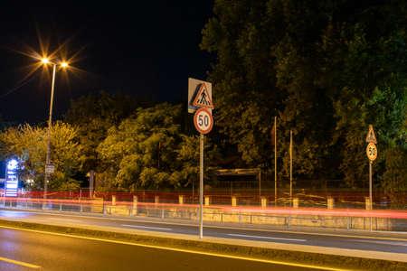50 km limitation traffic sign on the road. Light trails of cars and street lights shining around. Reklamní fotografie