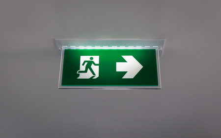 beautiful green emergency exit sign hanging on a ceiling photo