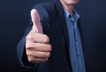 Hand of Asian businessman with thumbs up Stock Photo
