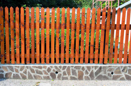 wood fence: fence of wooden slats on the stones  Stock Photo