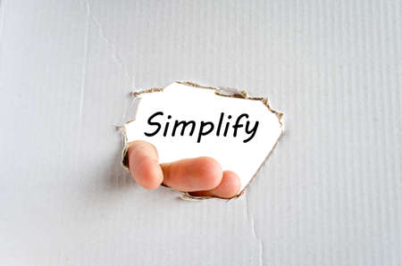 Hand and text Simplify on the cardboard background - business concept photo