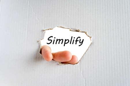 vereenvoudigen: Hand en tekst te vereenvoudigen op het karton achtergrond - business concept Stockfoto