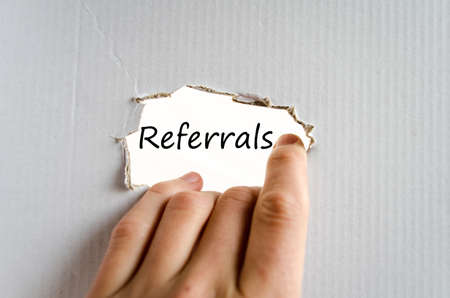 referrals: Hand and text Referrals on the cardboard background - business concept