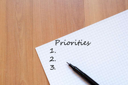 priorities: Priorities Concept White Blank Notepad On Office Wooden Table