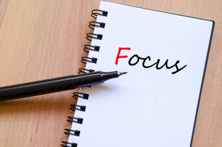 focus concept: White notepad and ink pen on the wooden desk Focus Concept Stock Photo