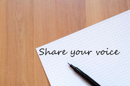 standpoint: White blank notepad on office wooden table Share your voice concept