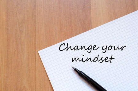 mindset: White blank notepad on office wooden table Change your mindset concept Stock Photo