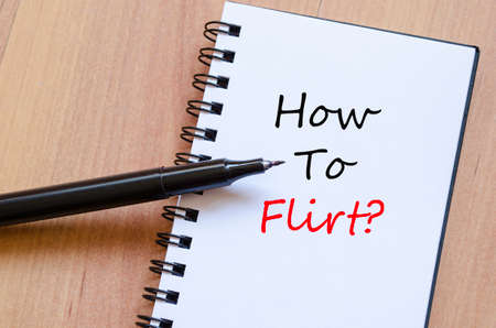 flirt: White notepad and ink pen on the wooden desk How To Flirt Concept Notepad