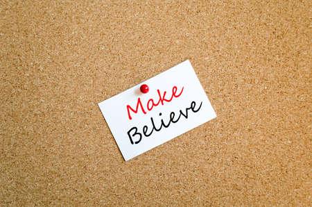 make believe: Sticky Note On Cork Board Background Make believe concept Stock Photo