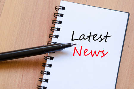 latest news: White notepad and ink pen on the wooden desk Latest News Concept
