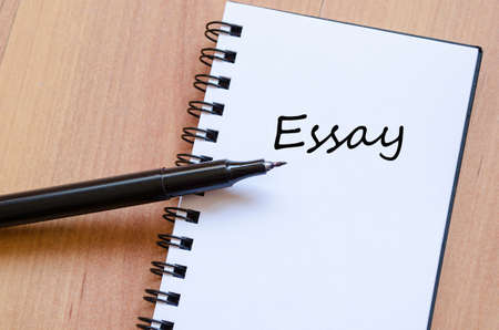 essay: White notepad and ink pen on the wooden desk Essay Concept Notepad Stock Photo