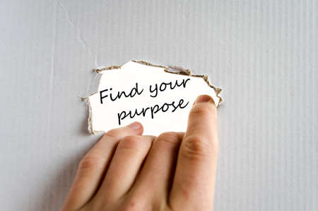 Hand and text on the cardboard background Find your purpose