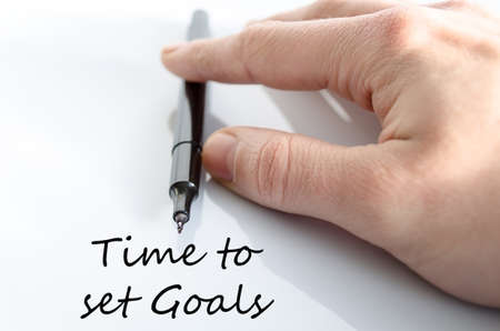accomplishing: Pen in the hand isolated over white background Time to set goals concept Stock Photo