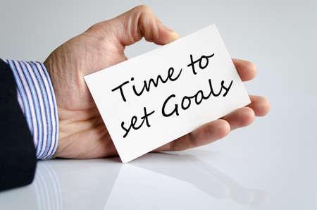 accomplishing: Business man hand writing Time to set goals
