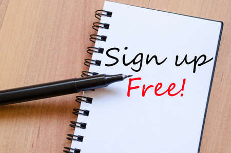 subscribe here: White notepad and ink pen on the wooden desk Sign up free concept Stock Photo
