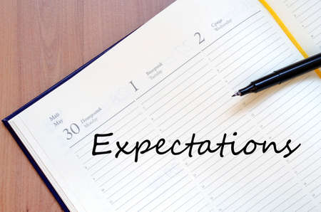 expectations: Yellow blank notepad on office wooden table Expectations concept