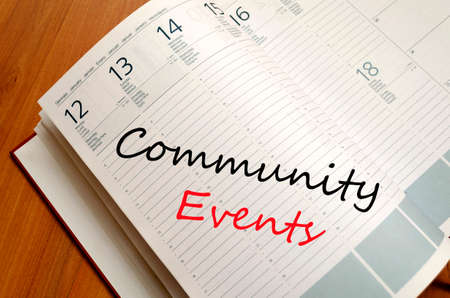 happening: Business Notepad on wooden table Community events concept