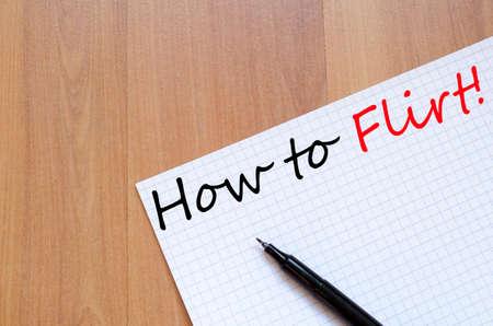 flirt: White blank notepad on office wooden table How to flirt concept