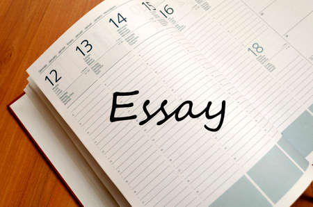 essay: Business Notepad on wooden table Essay concept Stock Photo