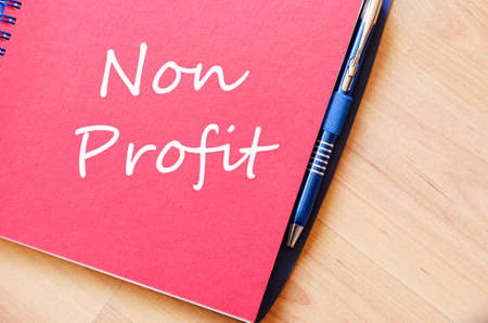 non profit: Red notepad and Non profit text concept