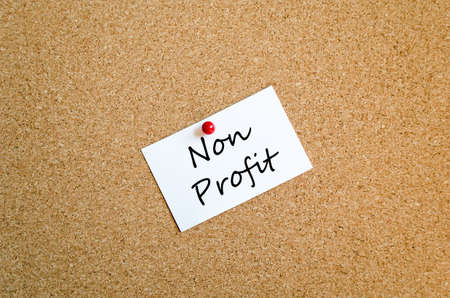 non profit: Sticky note on cork board background and text concept