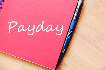 salaries: Notepad and pen on wooden background and text concept