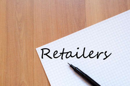 retailers: Notepad and pen on wooden background and retailers text concept