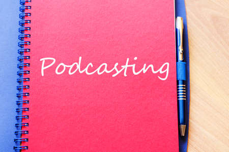 podcasting: Notepad and pen on wooden background and podcasting text concept