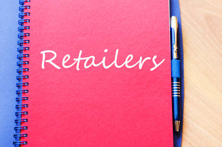 boutique display: Notepad and pen on wooden background and retailers text concept