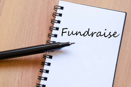 donation drive: Notepad and pen on wooden background and fundraise text concept