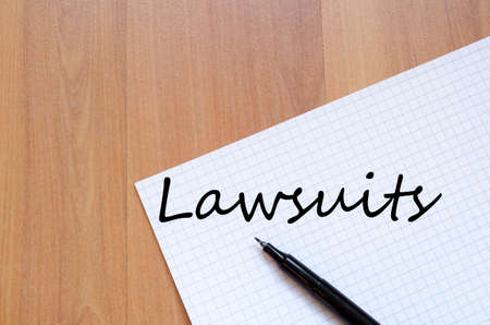 summons: Notepad and pen on wooden background and lawsuits text concept