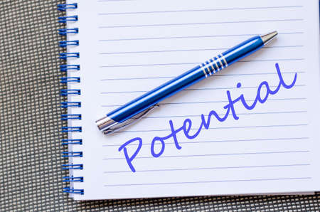 potential: Notepad and pen on wooden background and potential text concept