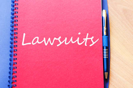 Notepad and pen on wooden background and lawsuits text concept