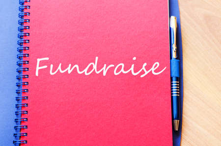 charity drive: Notepad and pen on wooden background and fundraise text concept