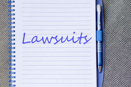lawsuits: Notepad and pen on wooden background and lawsuits text concept
