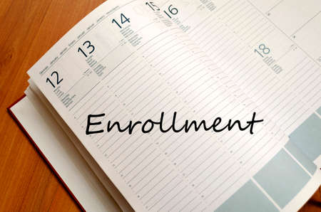 enrollment: Notepad and pen on wooden background and enrollment text concept