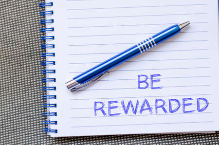 rewarded: Be rewarded text concept write on notebook with pen