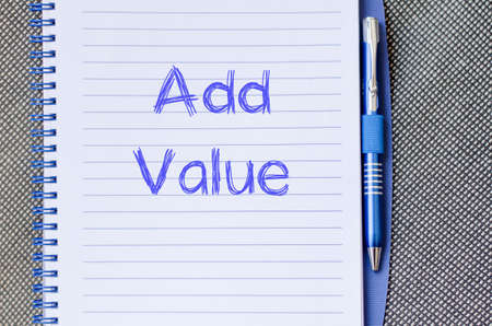 value add: Add valuer text concept write on notebook with pen