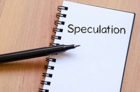 speculation: Speculation text concept write on notebook with pen