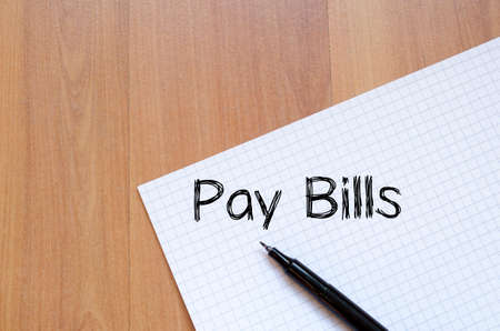 pay bills: Pay bills text concept write on notebook with pen Stock Photo