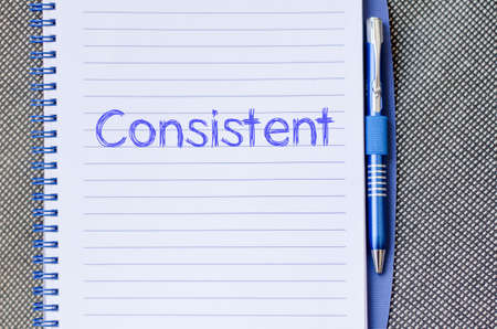 Consistente concepto de texto de escritura en el cuaderno con la pluma Foto de archivo