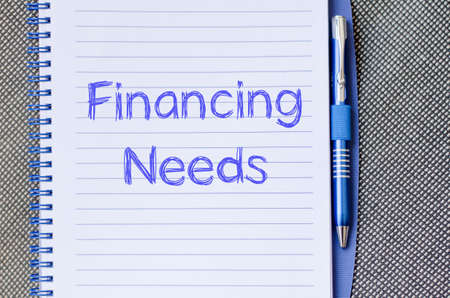 Financing needs text concept write on notebook with pen Stock Photo
