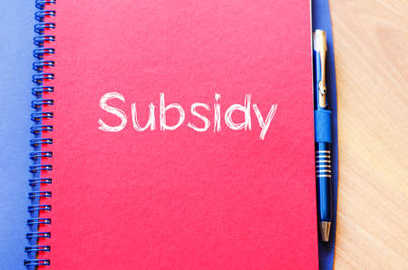 protectionism: Subsidy text concept write on notebook with pen