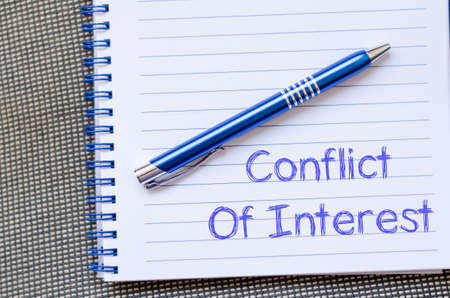 conflicting: Conflict of interest text concept write on notebook with pen