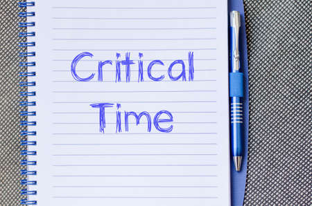 time critical: Critical time text concept write on notebook with pen