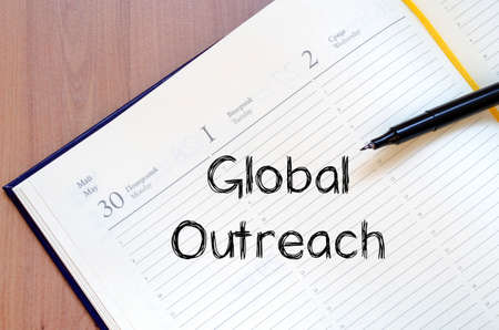 outreach: Global outreach text concept write on notebook with pen