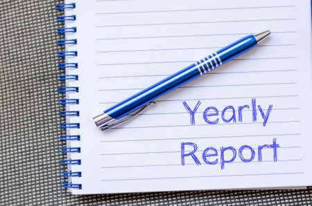 year financial statements: Yearly report text concept write on notebook with pen Stock Photo