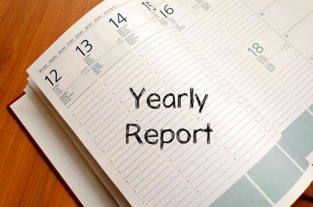 Yearly report text concept write on notebook with pen Stock Photo