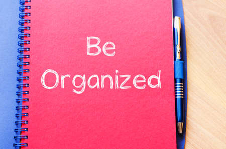 disorganized: Be organized text concept write on notebook with pen