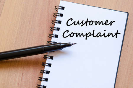 Customer complaint text concept write on notebook with pen